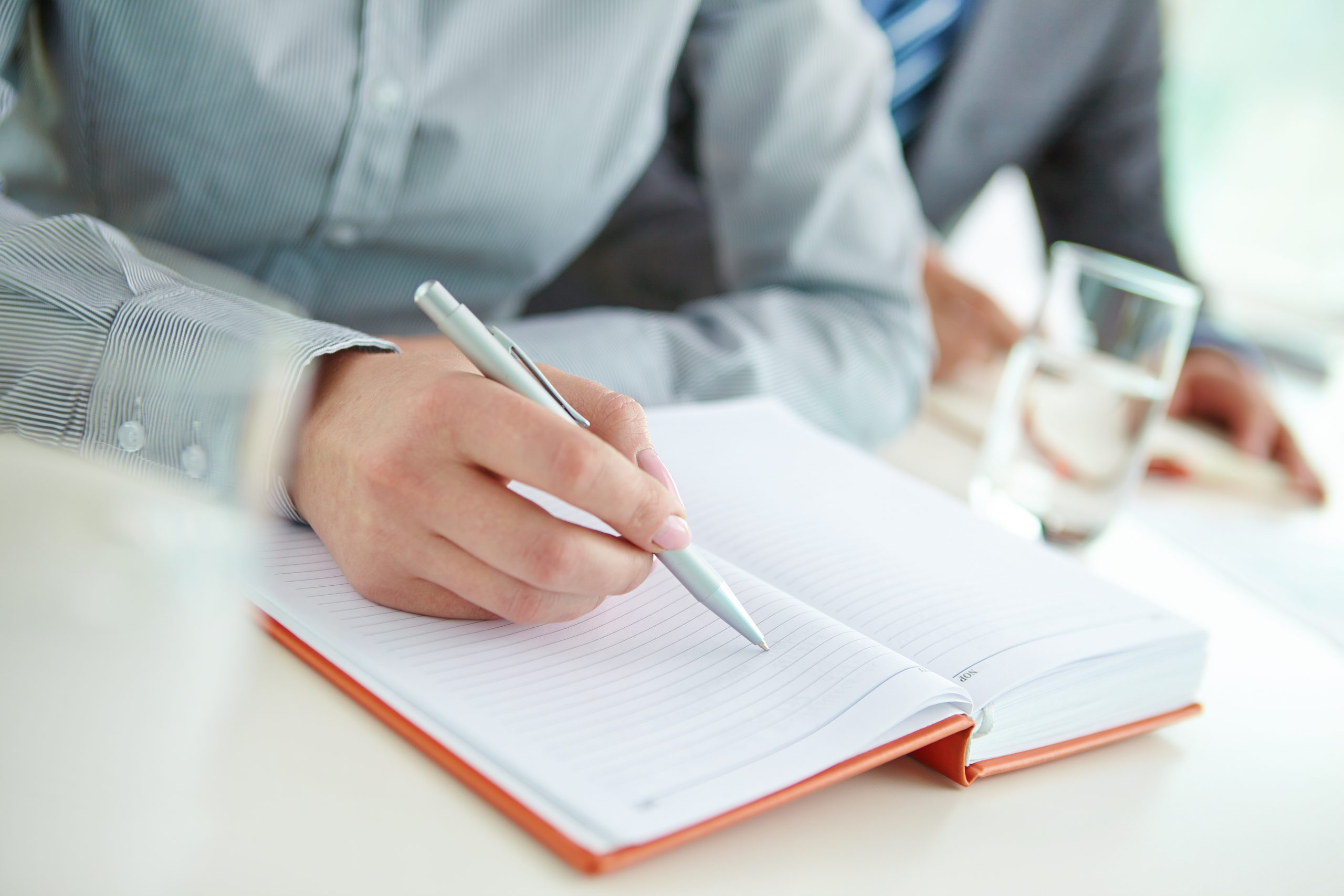 Businesswoman hand holding pen over empty notebook page